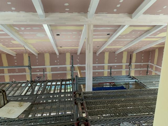 吹き抜けに足場を組み、梁を天井に取り付け