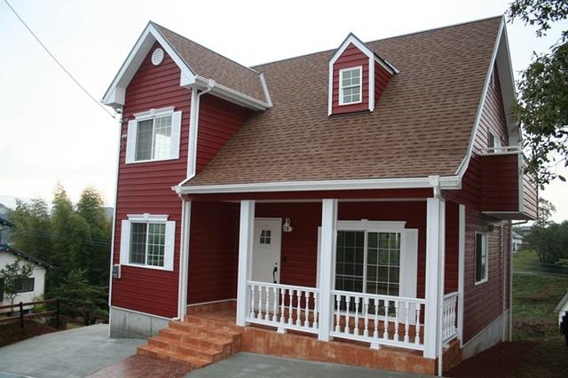 ワインレッドのラップサイディングが特徴的な輸入住宅